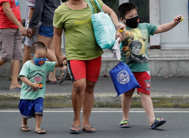 Children wearing protective masks cross a street in Mandaluyong, east of Manila, Philippines. The Philippines reported on Sunday, the first death of a new virus outside of China, where authorities delayed the opening of schools in the worst-hit province and tightened quarantine measures in another that allow only one family member to venture out to buy supplies.