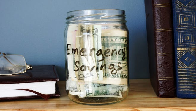 Glass labeled emergency savings jar filled with bills