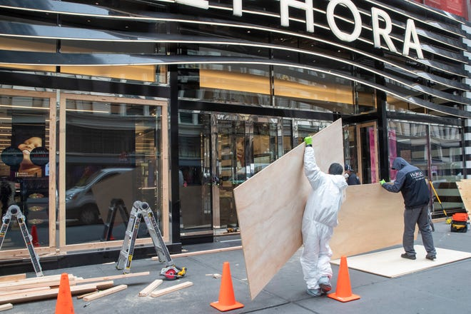 Carpenters in protective gear  board up a closed Sephora store on March 20, 2020, in New York.